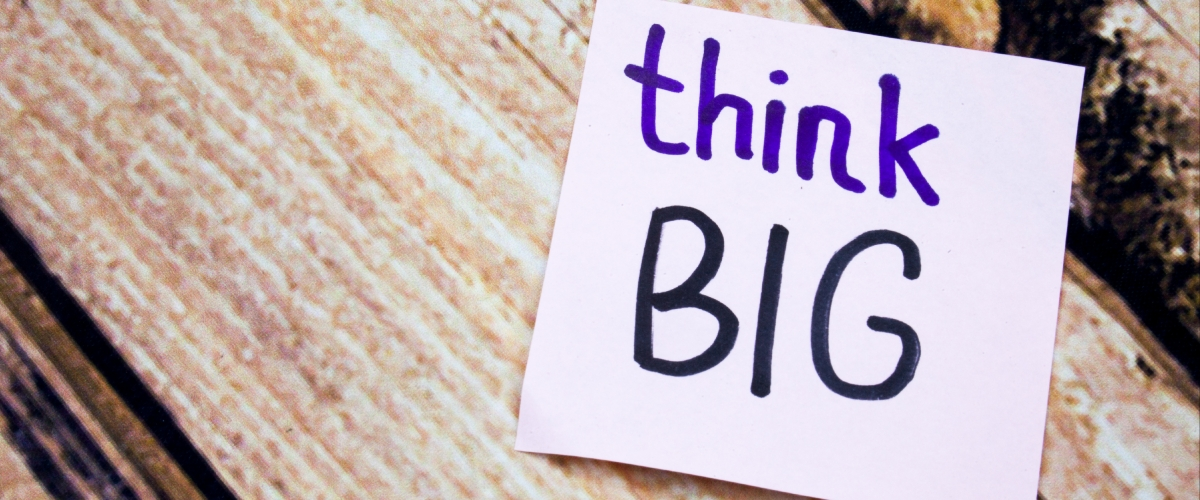"""A purple note sits in front of a wooden background. The note's text says """"think big."""""""