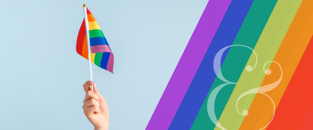 Graphic features a hand holding up a rainbow Pride flag and a rainbow design to the right of the image.