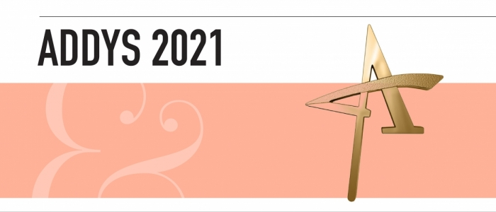 """A gold star sits in front of a rectangular pink background. A light pink ampersand is on the left. Above it, black text reads """"ADDYs 2021."""""""